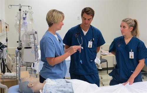 Photo above: Dr. Amy Palma (left) consults with nursing students in the Centre for Simulation Based Learning.